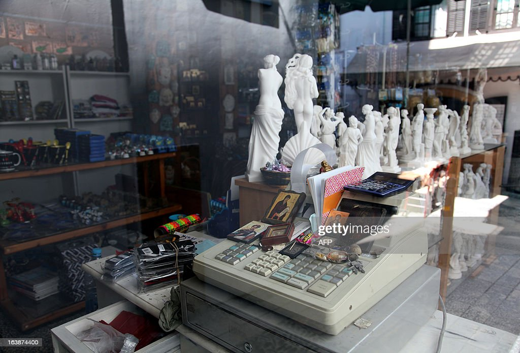 A picture taken behind a window shows a cash register at a souvenir shop in the Cypriot capital Nicosia on March 17, 2013. The Cyprus government postponed a planned emergency session of parliament to debate a controversial EU bailout, state media said, as the scale of opposition to its terms became clear.