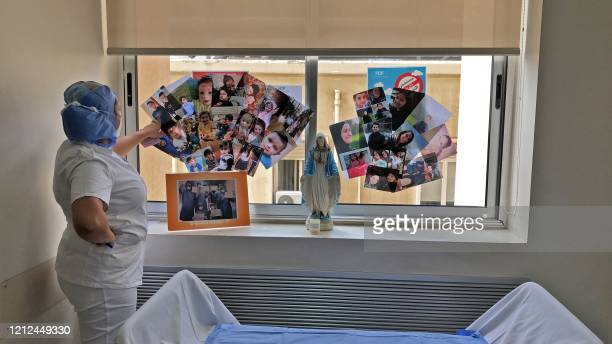 Picture taken by a nurse on April 30, 2020 at the Hotel Dieu de France Hospital, shows a colleague staring at family pictures displayed on a window...