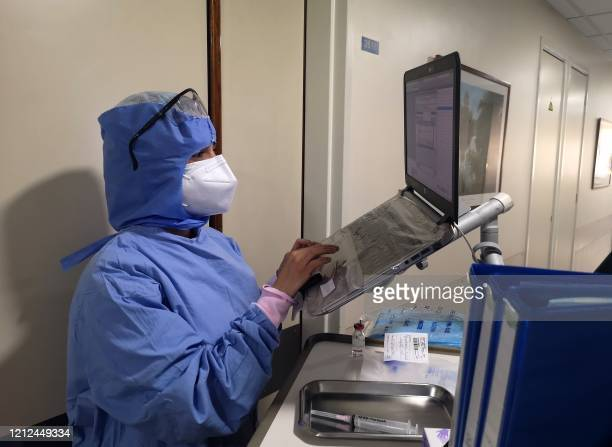 Picture taken by a nurse on April 8, 2020 at the Hotel Dieu de France Hospital, shows a colleague working on a laptop computer in the coronavirus...