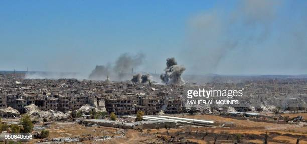 TOPSHOT A picture taken during a government guided tour near Damascus' southern alQadam neighbourhood shows smoke rising from buildings in Yarmuk a...