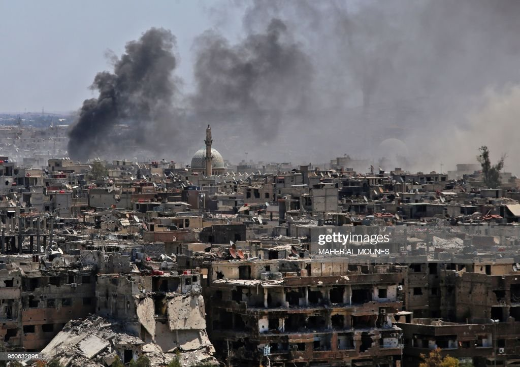 A picture taken during a government guided tour shows smoke rising from buildings in Yarmuk, a Palestinian refugee camp on the edge of Damascus, during regime shelling targeting Islamic State (IS) group positions in the southern district of the capital on April 24, 2018. - In 2015, IS overran most of Yarmuk, and the small numbers of other rebels and jihadists, including from Al-Qaeda's former affiliate, that had a presence there agreed to withdraw just a few weeks ago.