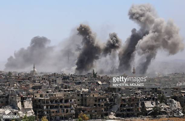 Picture taken during a government guided tour shows smoke rising from buildings in Yarmuk, a Palestinian refugee camp on the edge of Damascus, during...