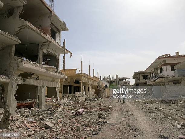 A picture taken during a press tour organized by the Russian Army shows Russian journalists standing on a devastated street on April 8 2016 in...
