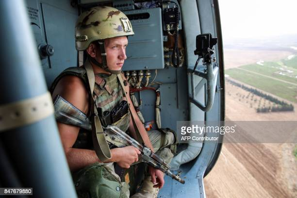 A picture taken during a press tour provided by the Russian Armed Forces on September 15 2017 shows a Russian soldier riding in a helicopter en route...
