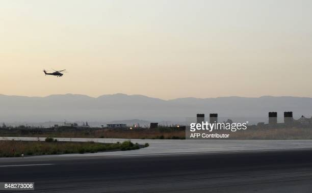A picture taken during a press tour provided by the Russian Armed Forces on September 12 2017 shows a Russian Kamov helicopter flies near S300...