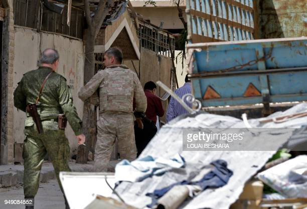 A picture taken during a Syrian armyorganised tour on April 20 2018 shows members of the Russian military police walking amidst destruction in the...