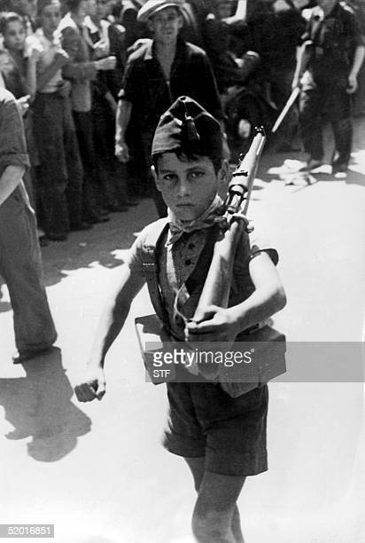Picture taken during the Spanish Civil War in the late 30s of a young Republican marching in a street of an unidentified village.
