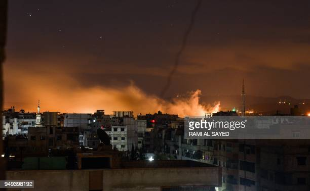 A picture taken early on April 21 2018 shows explosions appearing in the skyline of a southern district of the Syrian capital Damascus during regime...