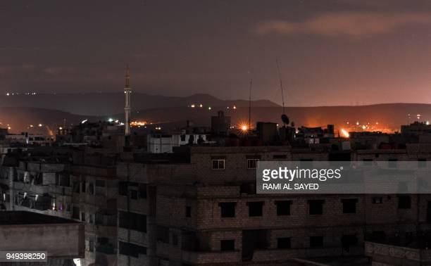 TOPSHOT A picture taken early on April 21 2018 shows explosions appearing in the skyline of a southern district of the Syrian capital Damascus during...