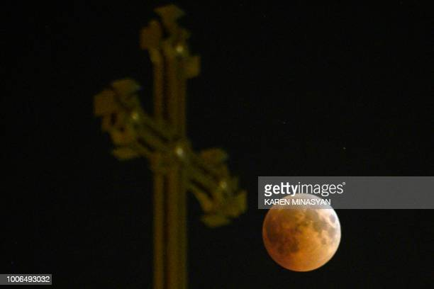 A picture taken early on July 28 2018 shows the moon during the total lunar eclipse also known as the 'blood moon' taken as it passes over an...