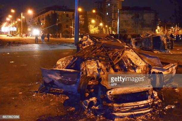 A picture taken early on March 12 2017 shows burned cars on a street in Georgia's Black Sea port of Batumi during clashes between police and...