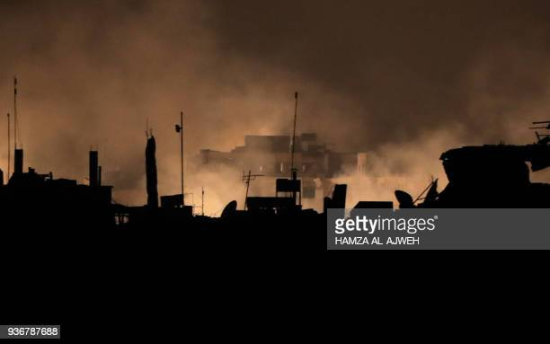 Picture taken early on March 23, 2018 shows flames erupting following regime bombardment in Douma, one of the few remaining rebel-held pockets in...