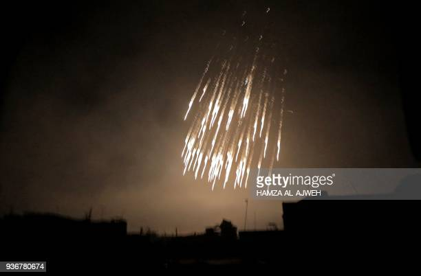 TOPSHOT A picture taken early on March 23 2018 shows what appears to be white phosphorus incendiaries landing during regime bombardment in Douma one...