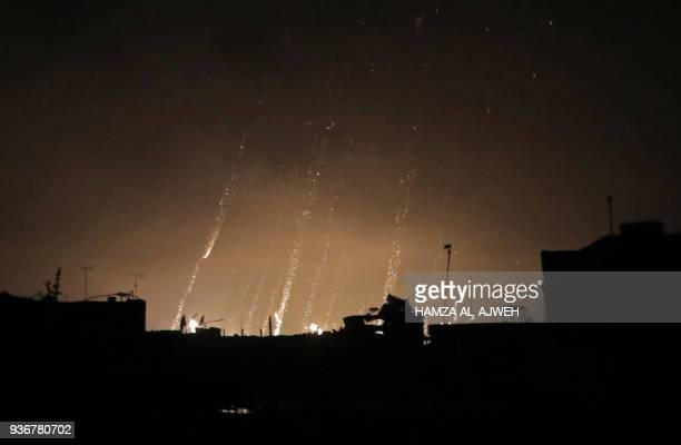A picture taken early on March 23 2018 shows what appears to be white phosphorus incendiaries landing during regime bombardment in Douma one of the...