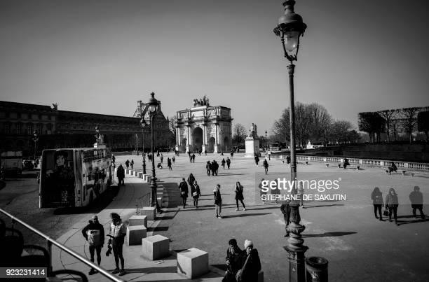 A picture taken from a doubledeck tourist bus on February 22 2018 shows people walking by the Arc de Triomphe du Carrousel by the Tuileries Garden in...