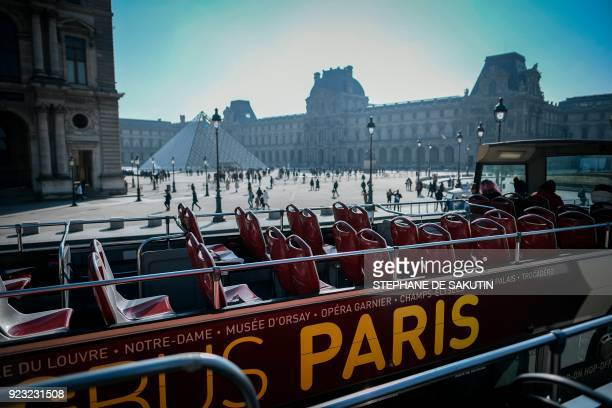 A picture taken from a doubledeck tourist bus on February 22 2018 shows people walking by the Louvre museum palace the Louvre Pyramid and the Cour...