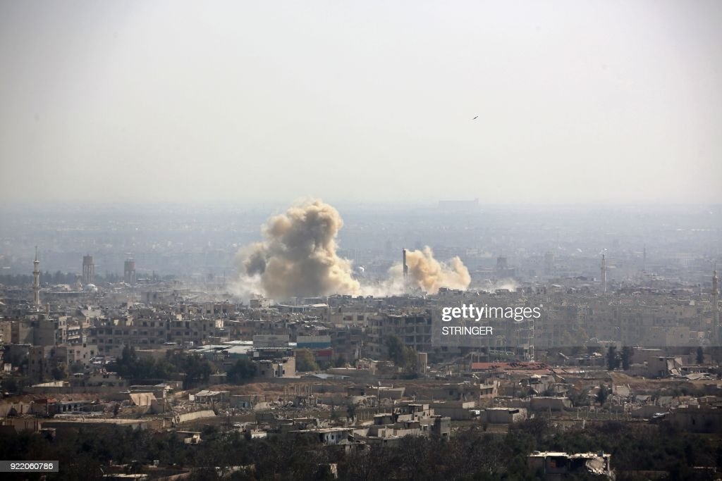 A picture taken from a government-controlled area on the outskirts of Harasta on the northeastern suburbs of Damascus on February 21, 2018, shows smoke rising from areas targeted by Syrian army shelling in the towns of Arbin and Harasta. /