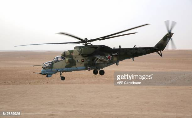 A picture taken from a helicopter during a press tour provided by the Russian Armed Forces on September 15 2017 shows a Russian Mil Mi24 Hind attack...