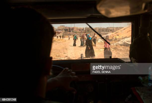 TOPSHOT A picture taken from a vehicle shows displaced Iraqis walking after evacuating their homes in a neighbourhood of west Mosul on May 17 during...