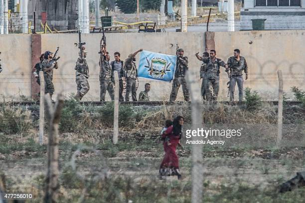 A picture taken from Akcakale district of Turkey's southeastern city Sanliurfa shows a group of armed men open the flag of the Free Syrian Army in...