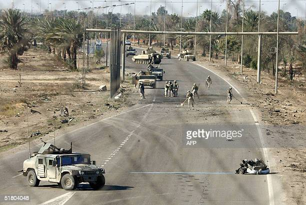 Picture taken from behind a fence shows the sire where a car bomb exploded near a US military convoy on the perilous road to Baghdad airport 30...