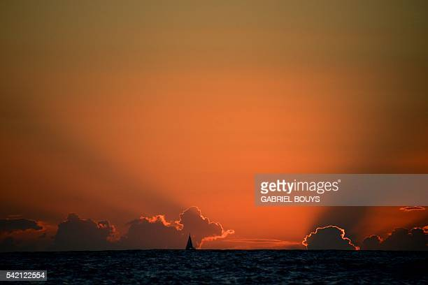 A picture taken from Ginostra shows a boat sailing at sunset on June 19 2016 off the Stromboli island Stromboli is part of the Aeolian Islands a...