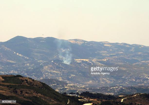 A picture taken from Hatay province of Turkey which has borders with Latakia shows that smoke rises as the forest fire begins after the Assad...