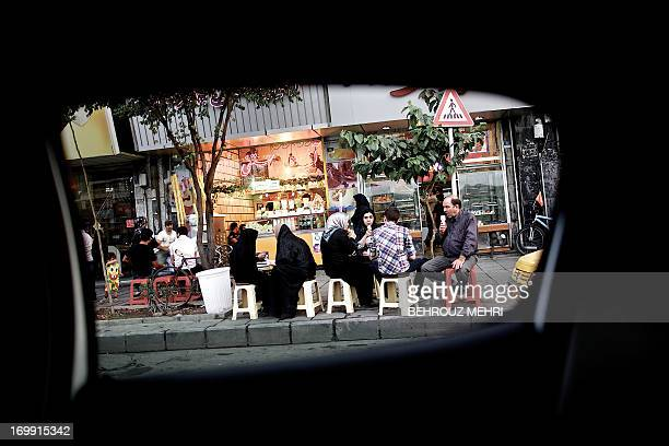 A picture taken from inside a car shows Iranians having ice cream at the historical Baharestan square in downtown Tehran on June 4 2013 AFP...