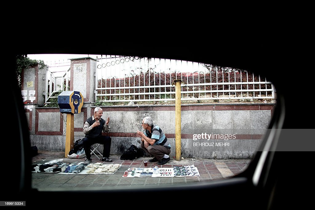 A picture taken from inside a car shows Iranians vendors drinking tea on a sidewalk in Azadi (Freedom) square in western Tehran on June 4, 2013.