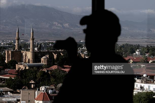 A picture taken from inside Shacolas Tower in the Cypriot capital Nicosia on July 18 shows a tourist taking a picture of Saint Sophia Roman Catholic...
