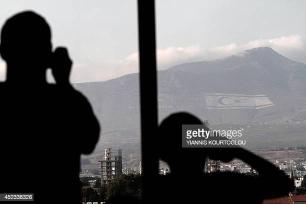 A picture taken from inside Shacolas Tower in the Cypriot capital Nicosia on July 18 shows a tourist taking a picture of the flag of the...