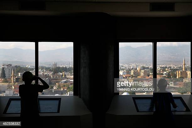 A picture taken from inside Shacolas Tower in the Cypriot capital Nicosia on July 18 shows tourists taking pictures of buildings in the...
