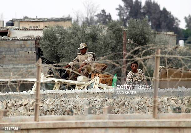 A picture taken from Rafah in the southern Gaza Strip on the border with Egypt on July 8 shows Egyptian soldiers keeping watch on top of a tank on...