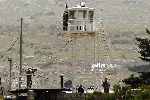 A picture taken from the Druze town of Majdal Shams in the Israeliannexed Golan Heights shows UN soldiers watching as Israeli soldiers from the...