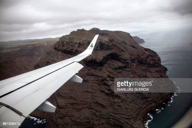 TOPSHOT A picture taken from the inaugural first commercial flight between Johannesburg and Saint Helena shows the cliffs of the volcanic tropical...