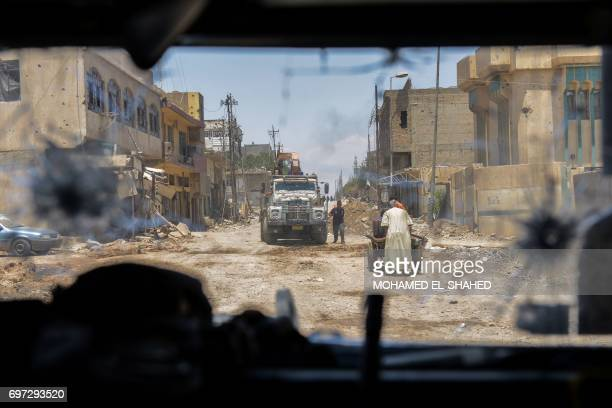 Picture taken from the inside of an Iraqi forces armoured vehicle shows residents walking through a damaged street as troops advance towards Mosul's...