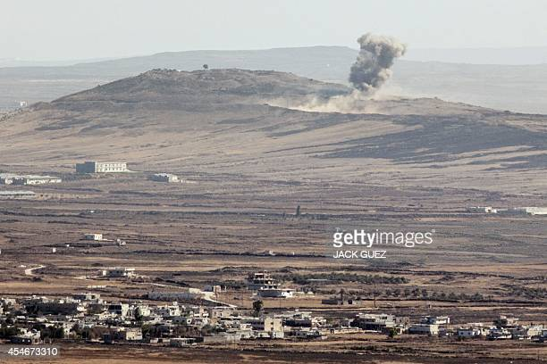 A picture taken from the Israeliannexed Golan Heights shows smoke billowing from the Syrian village of Qahtaniah following explosions during fighting...