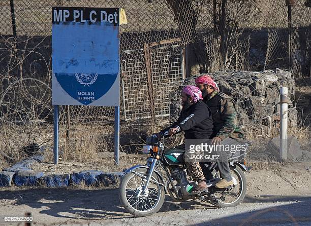 A picture taken from the Israelioccupied Golan Heights shows armed men reportedly rebel fighters driving a motorcycle near an abandoned UN building...
