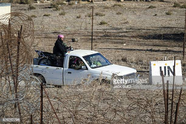 A picture taken from the Israelioccupied Golan Heights shows armed men reportedly rebel fighters driving a pick up truck in the Syrian side of the...