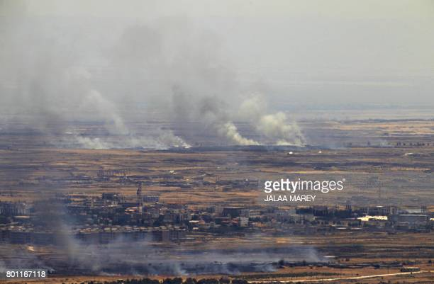 A picture taken from the Israelioccupied Golan Heights shows smoke billowing from the Syrian side of the border on June 26 2017 Israeli forces fired...