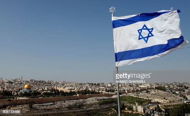A picture taken from the Mount of Olives shows an Israeli flag fluttring as Jerusalem's Old City is seen in the background on January 22 2018 / AFP...