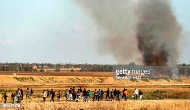 A picture taken from the Palestinian side of the border with Israel near the southern Gaza Strip town of Khan Yunis shows fire and smoke in a field...