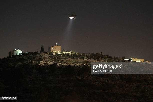 A picture taken from the Palestinian village of Dahriya shows an Israeli army helicopter flying in the area of the Otniel Jewish settlement in the...