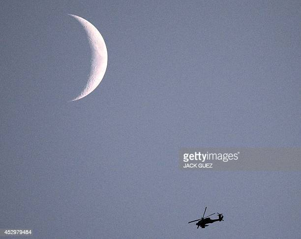 A picture taken from the southern Israeli Gaza border shows an Israeli Apache helicopter flying under a crescent moon over Gaza Strip on July 31 2014...