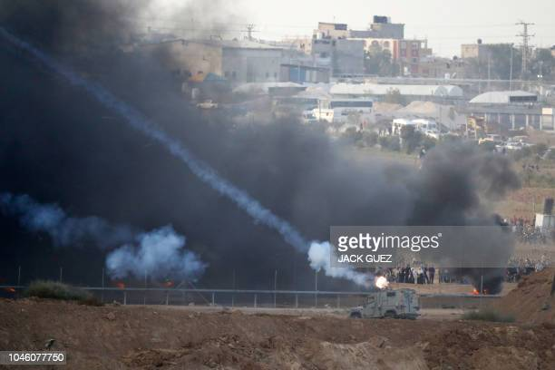 TOPSHOT A picture taken from the southern Israeli kibbutz of Nahal Oz across the border with the Gaza Strip shows Israeli forces firing tear gas...