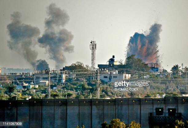TOPSHOT A picture taken from the southern Israeli village of Netiv Haasara shows an explosion and smoke fumes caused by an Israeli airstike across...