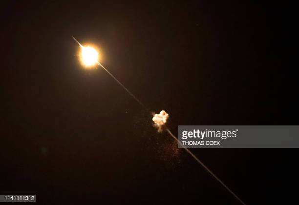 Picture taken from the southern Israeli village of Netiv Haasara shows missiles fired from Israel's Iron Dome air defence system, designed to...