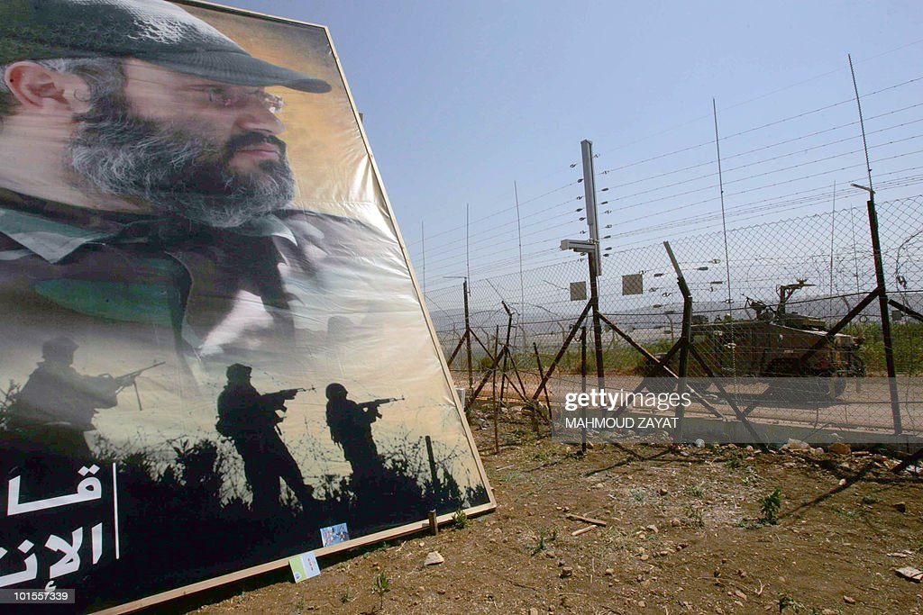 A picture taken from the southern Lebanese village of Kfarkilla shows an Israeli military patrol driving past a giant poster of assassinated Hezbollah military commander Imad Mughniyeh, on their side of the border with Lebanon on May 25, 2010. Lebanon is marking on May 25 the 10th anniversary of the withdrawal of Israeli forces from its south.