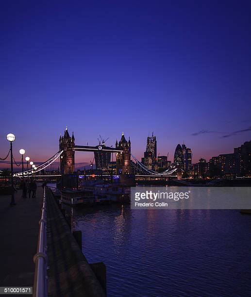 Picture taken from the Thames' bank, depicting Tower Bridge and a part of the City financial district skyscrapers, under a warm and dark light...
