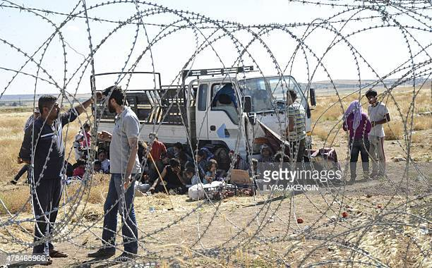 A picture taken from the Turkish side of the border in Suruc Sanliurfa province shows Syrian Kurds waiting on the Syrian side after they escaped the...